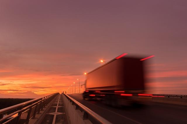 A semi truck blurring by at dusk