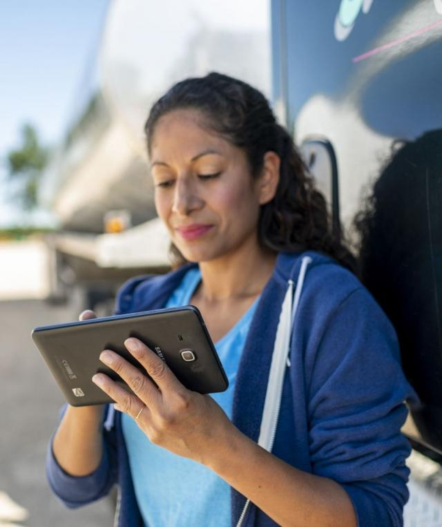 Woman Using Tablet Outside of Truck