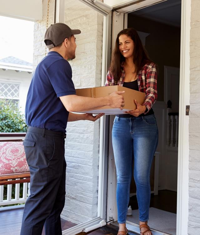 Woman receiving packages at home from delivery driver