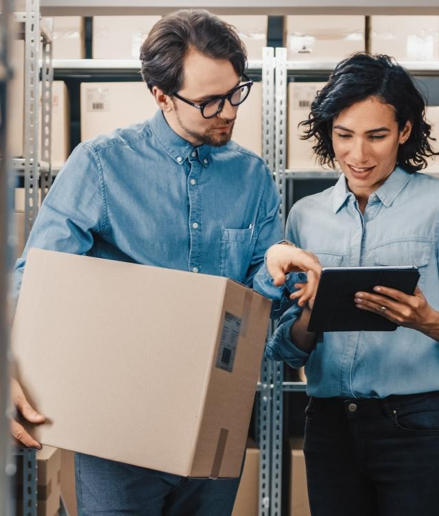 two people checking TMS status in warehouse with boxes