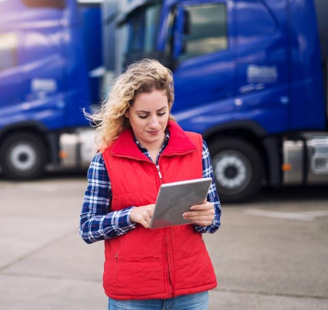woman driver in front of trucks with Trimble tablet
