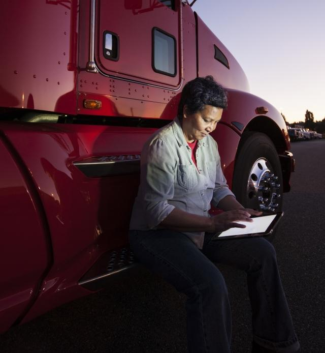 Driver with tablet outside of truck at sunset